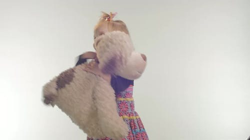 Little girl playing with a plush puppy