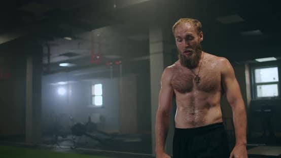 Thumbnail for Müde männlichen Athleten in der Turnhalle ruht und bereitet sich auf eine Übung vor. Zeitlupe verschwitzt Athlet