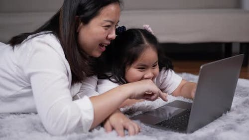 Junge Mutter und kleine Tochter spielen auf Laptop