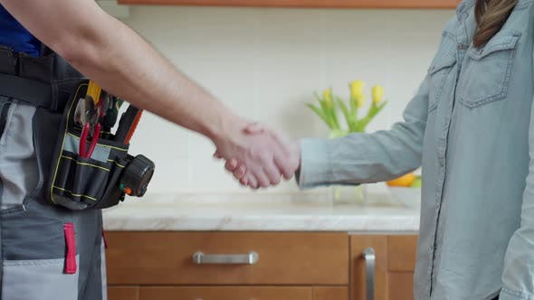 Close Up of Plumber and Client Shaking Hands in Kitchen