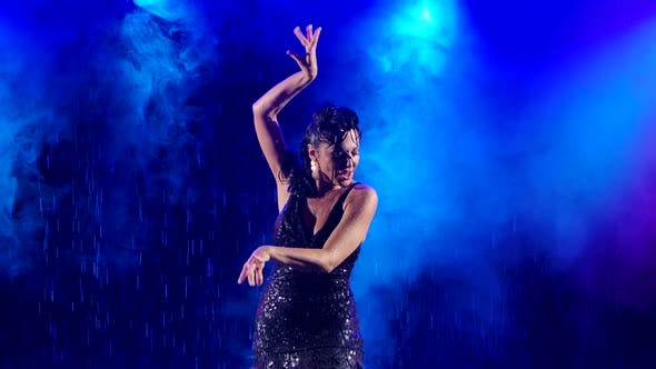 Wet Passionate Woman Practicing Flamenco Dance in a Smoky Studio in the Rain. The Dancer Enjoys