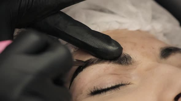 Thumbnail for Close-up, the Hands of the Cosmetologist in Black Rubber Applying Permanent Make Up on Eyebrows-
