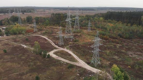 Long distance transmission lines. High-voltage pillars in forest. Power transmission pylons