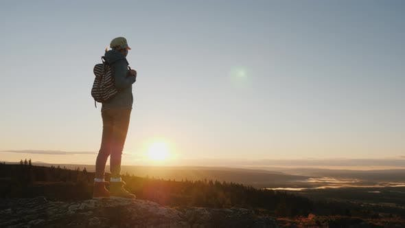 Cover Image for A Woman Traveler Stands on Top of a Mountain