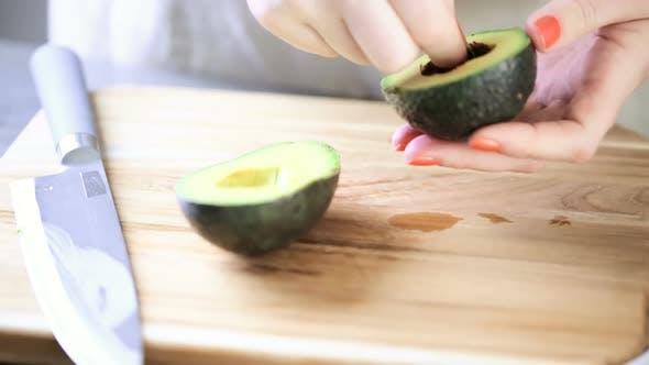 Thumbnail for Cutting fresh avocado on a wood cutting board.