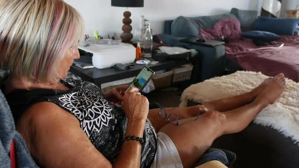 Thumbnail for Senior Woman Looking on Mobile Phone Relaxing on Sofa at Home
