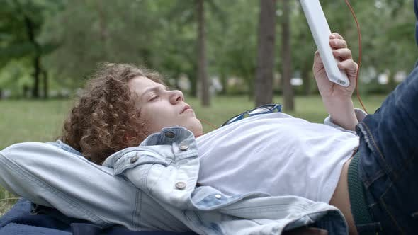 Thumbnail for Boy Watching Video on Tablet while Resting in Park