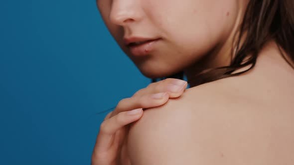 Close-up of Woman Arm Softly Massaging Shoulder Isolated on Blue