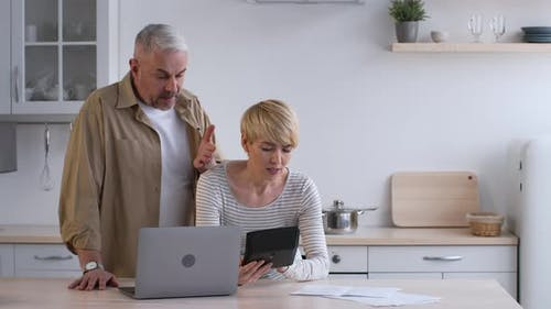Discontented Couple Calculating Expenses Suffering From Crisis Paying Bills Indoors