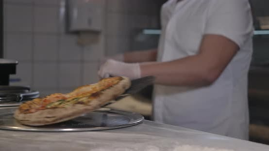 Male Caucasian Chef Putting Fresh Baked Pizza on Table and Leaving