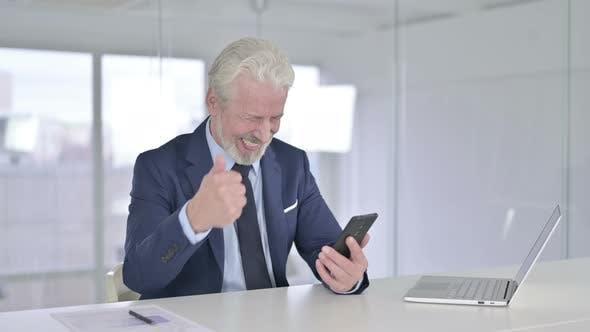 Old Businessman Celebrating Success on Smartphone