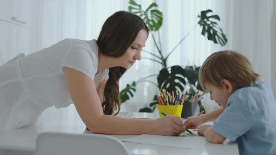 Thumbnail for Mom Helps Son To Perform Preschool Homework To Draw a Pencil Drawing Sitting at the Table