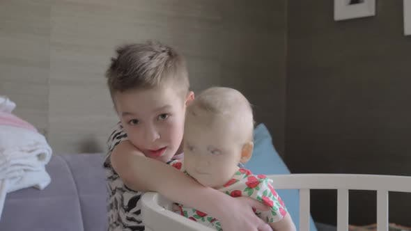 A Boy Hugging His Baby Sister in a Crib