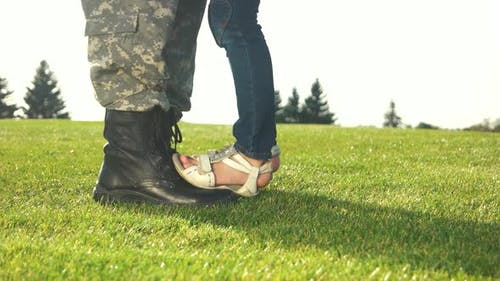 Soldier Feet with Boots and Little Daughter with Sandals