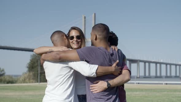 Thumbnail for Happy Four Friends Hugging While Standing on Meadow