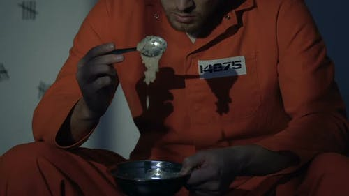 Caucasian Prisoner Looking With Disgust at Food, Awful Conditions in Jail