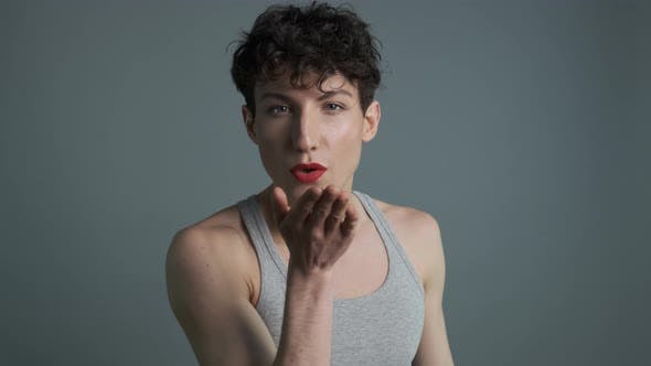 Portrait of Handsome Transgender Man with Makeup Sending Air Kiss To Camera