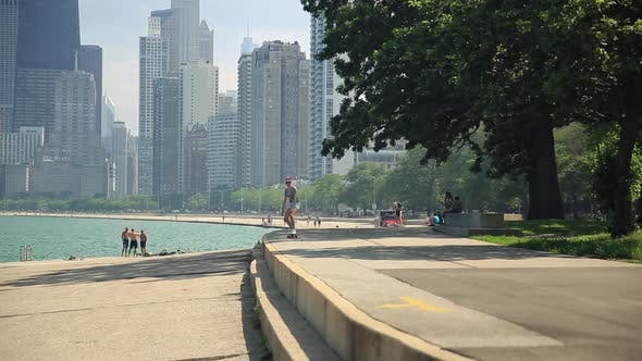 Thumbnail for A young woman goes longboard skateboarding with the Chicago, Illinois skyline in the background.
