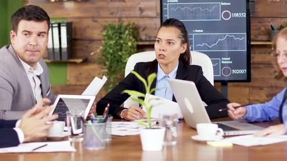Female Team Leader Giving His Team Financial Charts