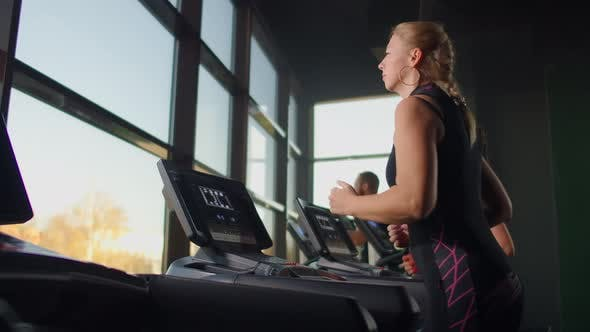 Thumbnail for Nettes junges Mädchen, das auf einem Laufband vor Panoramafenstern im Fitnessraum läuft. Fitnessstudio mit