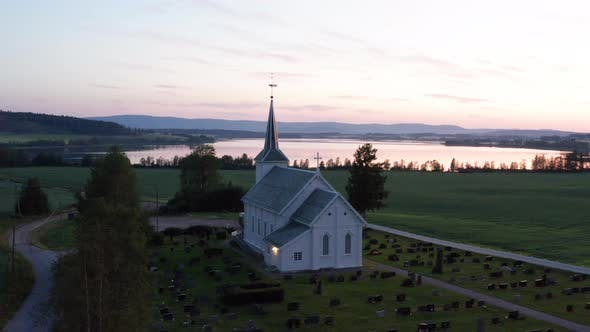 Scenic View From Above of Norwegian Church with Mountains and Lake Background