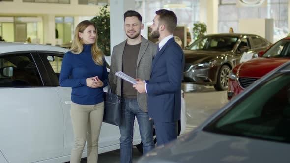 Thumbnail for Salesman Helping Couple Choosing Car at Dealership