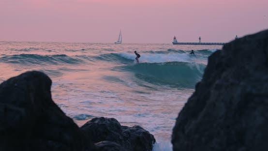 Thumbnail for Young People in Wetsuit Surf on Sunset Beach