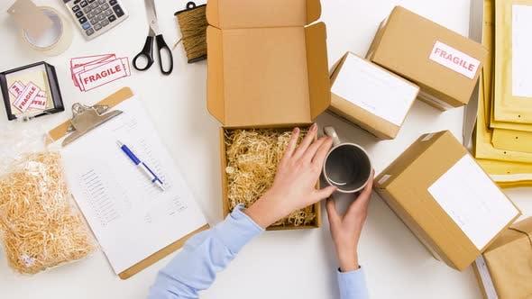 Thumbnail for Woman Packing Mug To Parcel Box at Post Office 7