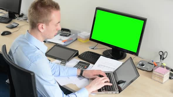 Thumbnail for Young Handsome Man Works on Laptop Computer in the Office - Green Screen - Computer and Tablet