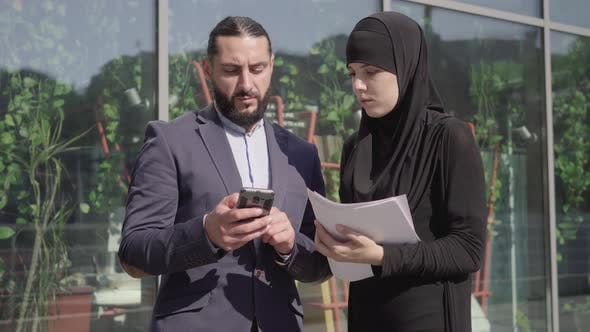 Thumbnail for Middle Shot of Confident Muslim Woman with Documents and Man with Smartphone Discussing Business