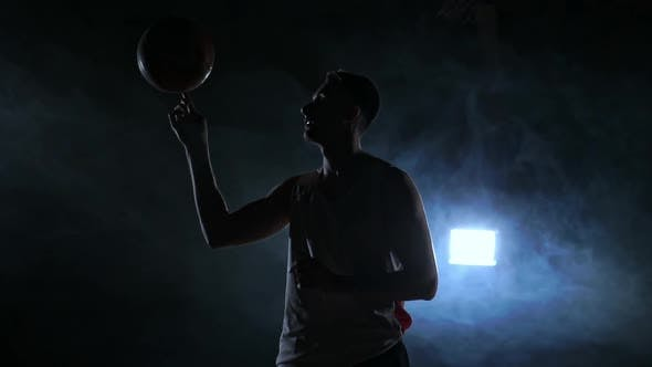 Cover Image for Hooded Basketball Player Spinning the Ball at Night in an Empty Car Park, in Slow Motion