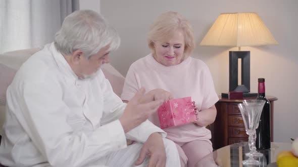 Thumbnail for Porträt der überraschten kaukasischen Senior Woman Öffnung Geschenkbox. Frau erhalten elegante Schal auf Saint