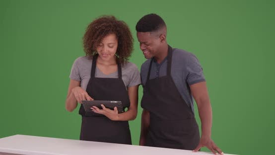 Black man and woman plan their recipe on their tablet on green screen
