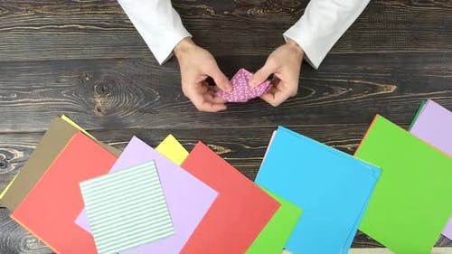Man Folding Origami From Pink Paper.