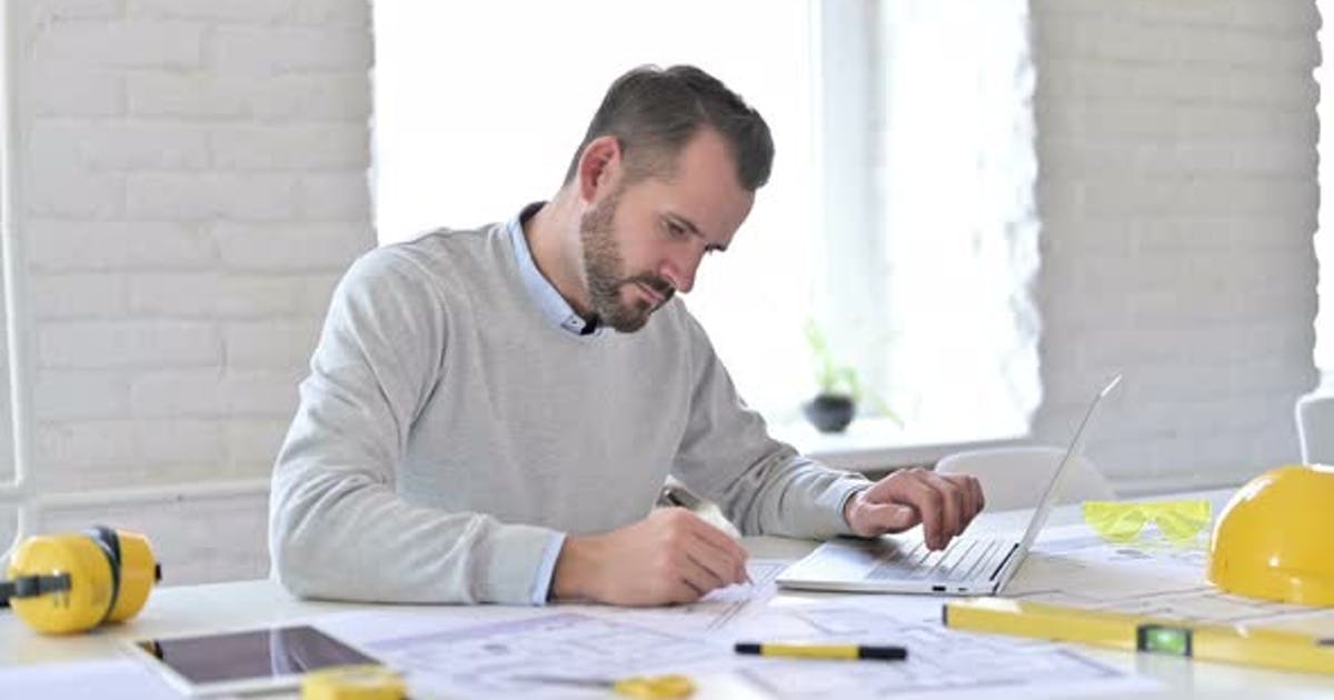 Young Architect with Laptop Doing Paperwork in Office