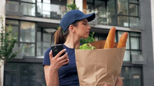 Food Delivery Woman Courier Uses Smartphone Holds Paper Bag Looking Address