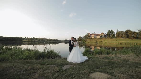 Thumbnail for Caucasian Groom with Bride in the Park Near Lake. Wedding Couple. Newlyweds Kiss