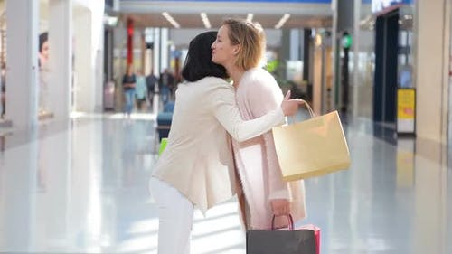 Two Happy Young Girls Meet with a Hug in a Department Store While Shopping