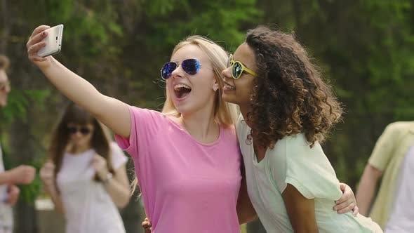 Thumbnail for Zwei schöne junge Damen tanzen, lachen und posieren für Selfie auf Smartphone