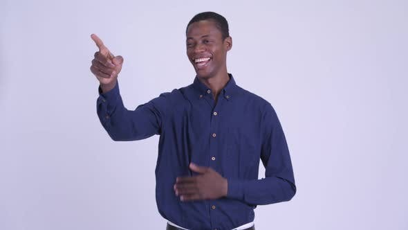 Young Happy African Businessman Laughing and Pointing Finger