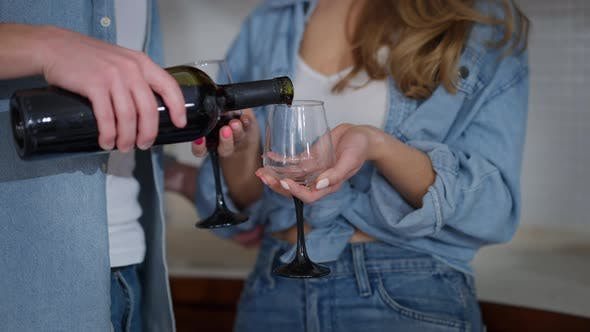 Closeup Male Hand Pouring Red Wine in Two Glasses in Female Hands