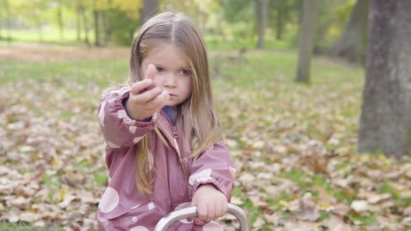 Little Caucasian Girl Shows a Handful of Acorns to Camera with a Smile Before Giving Them to Her Mom