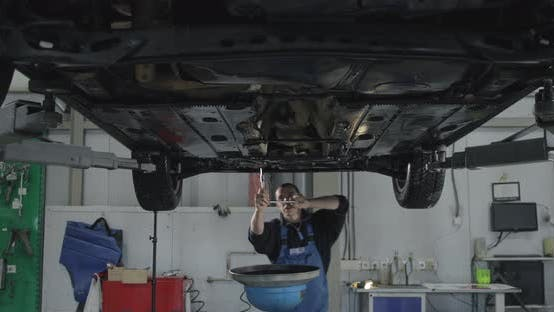Professional Serviceman Screwing Details Of Car With Special Tool
