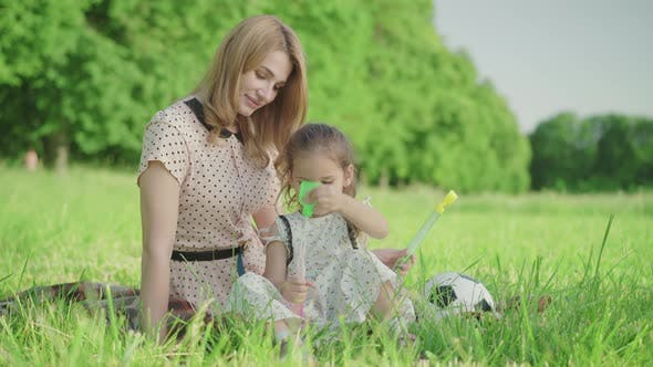 Thumbnail for Joyful Young Mother Helping Cute Little Girl To Blow Soap Bubbles. Portrait of Cheerful Happy
