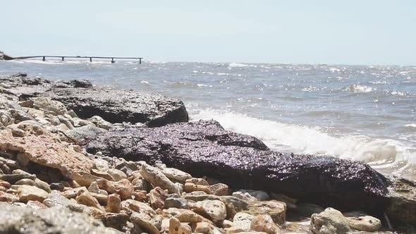 Large Rocks Boulders on the Seashore Waves Crashing Against Rocks Slow Motion on a Sunny Day