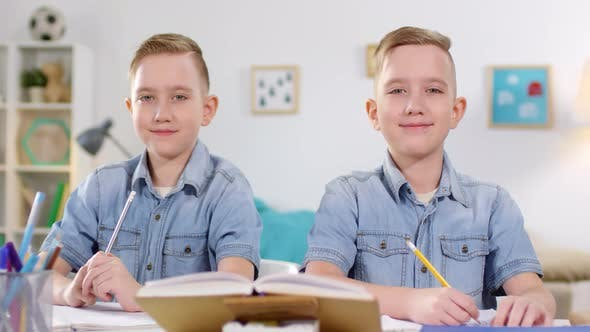 Thumbnail for 10-Year-Old Caucasian Twins Studying and Posing for Camera