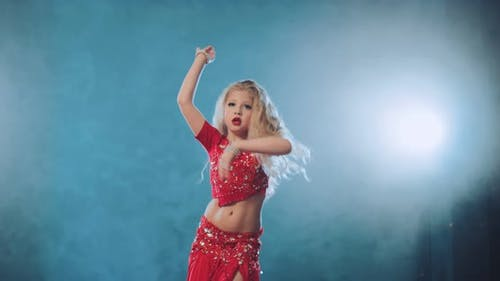 Beautiful and Cheerful Girl Waving Her Hair and Head in an Oriental Dance