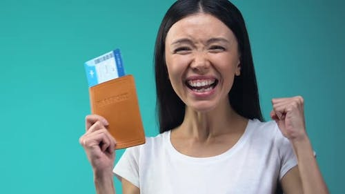 Excited Asian Lady Holding Passport and Flight Tickets, Work Abroad, Emigration