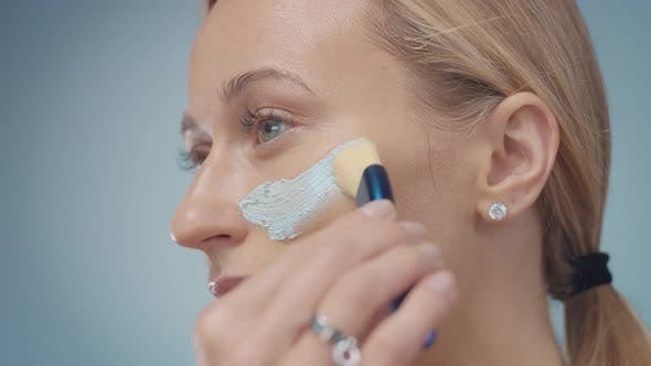 Blonde Model in Studio Makes a Cleansing Facial Mask