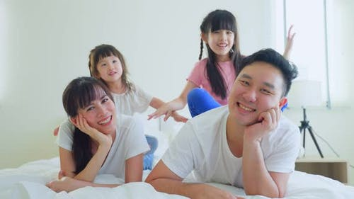 Portrait of Asian happy family, Parents and young little girl sibling daughters enjoy playing on bed